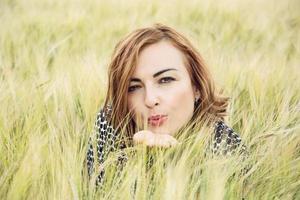 jovem manda um beijo doce no campo de trigo foto
