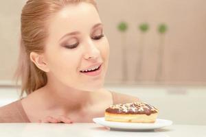 senhora sorridente olha rosquinha com a intenção de comer foto