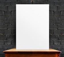cartaz em branco na mesa de madeira na parede de tijolo preto