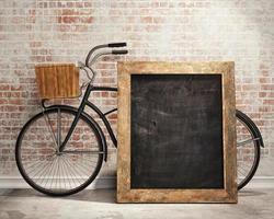 parede de tijolos com um quadro negro e bicicleta à moda antiga