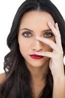 modelo de cabelos escuro com lábios vermelhos, escondendo o rosto foto