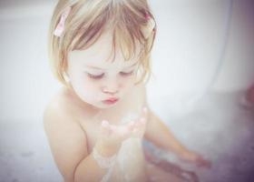 menina brincando com bolhas foto