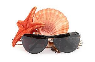 óculos de sol na estrela do mar e concha foto