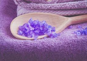 sal de banho purpe perfumado de lavanda em uma colher de pau foto