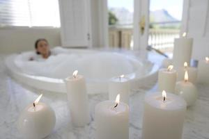 jovem mulher no banho de espuma, velas iluminadas em primeiro plano foto
