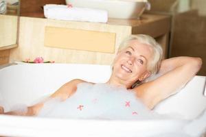 mulher sênior relaxante no banho de espuma foto