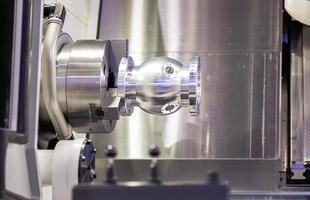 operador que gira o autopart de alumínio pelo torno do cnc