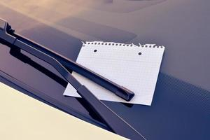 folha de papel sob um limpador de para-brisa foto