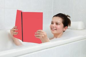 jovem mulher na banheira lendo livro