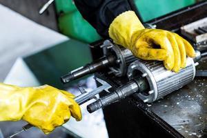 trabalhador operando a máquina de perfuração na fábrica foto