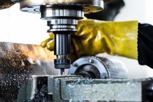 trabalhador operando a máquina de perfuração na fábrica
