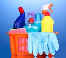 cesta com itens de limpeza em fundo azul foto