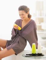 mulher jovem feliz, verificando cosméticos de banho no banheiro