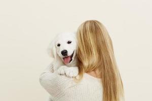 filhote de cachorro labrador fofo abraçado por mulher loira foto