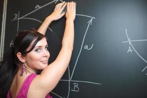 professor muito jovem, escrevendo no quadro-negro foto