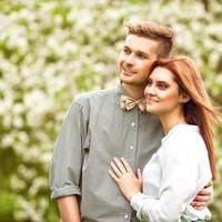 casal apaixonado no parque sorrindo segurando um buquê foto
