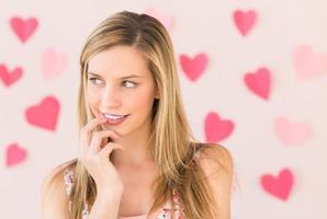 mulher pensativa com papéis em forma de coração contra est colorido foto