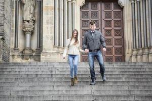 comprimento total do jovem casal descendo degraus contra construção foto