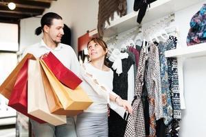 casal escolhendo roupas na loja foto