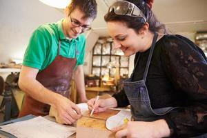 dois jovens sapateiros preparando sapato dura em uma oficina foto