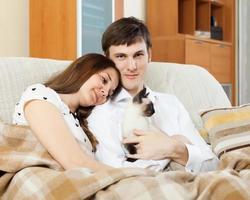 casal com gatinho na sala de estar foto
