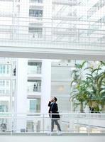 empresário andando com telefone móvel foto