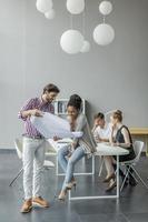 um trabalhador de escritório mostrando um plano para seu colega foto