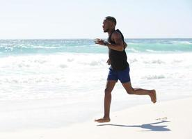 jovem correndo descalço na praia foto
