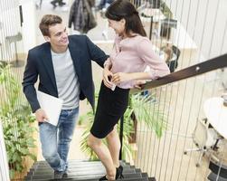 comprimento total do casal jovem de negócios na escada foto