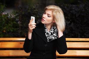 jovem mulher loira olhando para o telefone móvel foto