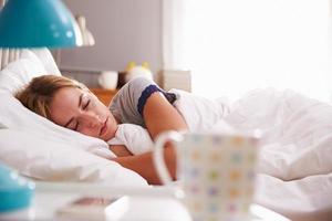 jovem mulher dormindo na cama foto