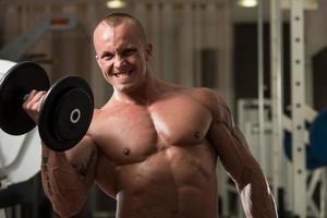 jovem malhando bíceps halteres concentração cachos foto