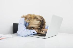 empresária cansada, descansando a cabeça no laptop na mesa de escritório foto