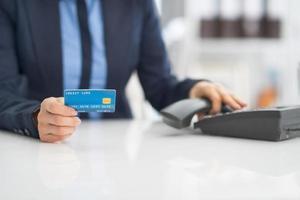 closeup na mulher de negócios com telefone de discagem de cartão de crédito