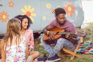 hipster tocando violão para seus amigos foto