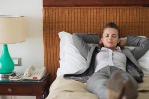 mulher de negócios cansado dormindo no quarto de hotel foto