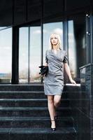 jovem empresária na escadaria contra janelas do escritório foto
