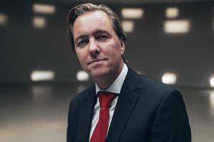 empresário arrogante, vestindo terno com gravata vermelha na sala vazia. foto