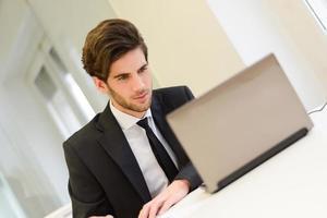 empresário sentado no seu laptop e trabalhando em seu escritório foto