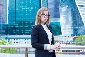 jovem mulher com café nos arranha-céus de negócios de fundo foto