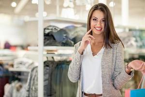 mulher jovem sorridente com sacos de compras sobre fundo de shopping