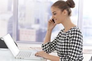 jovem empresária com laptop e celular foto