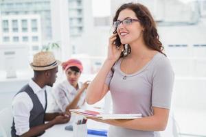 empresária sorridente telefonando e segurando o bloco de notas foto
