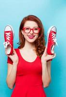 menina ruiva sorridente com sapatos desportivos