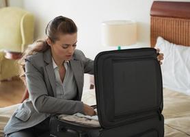 mulher de negócios descompactar bagagem no quarto de hotel foto