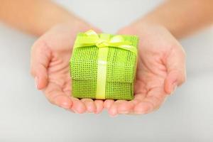 presente verde colorido nas mãos em concha