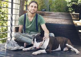 jovem tomando café com seu cachorro foto