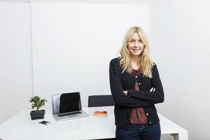 retrato de mulher de negócios feliz em pé braços cruzados no escritório