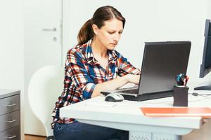 foto de mulher digitando no laptop no escritório