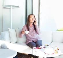 empresária falando no celular em uma casa de café foto